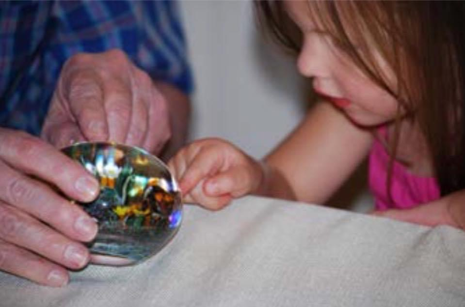 A child exploring a paperweight.
